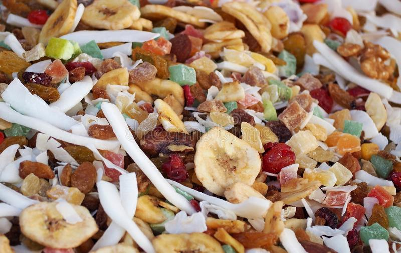 Dried fruit mix with pieces of banana, coconut, nuts, blueberries, raisins, kiwi,cherry and others. Colorful food background stock images