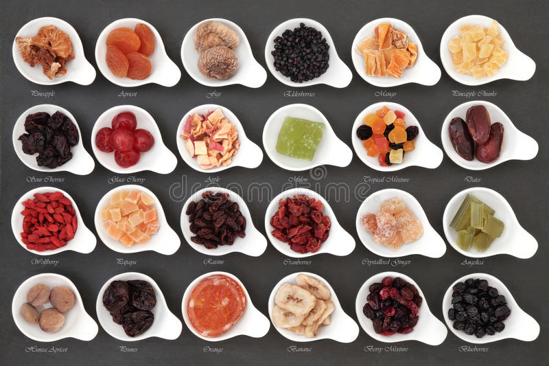 Dried Fruit Sampler. Large dried fruit selection in white bowls over slate background with titles stock photos