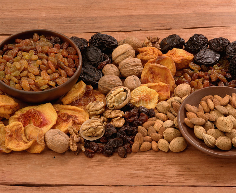 Dried fruits. Assorted dried fruits over wood background royalty free stock photo