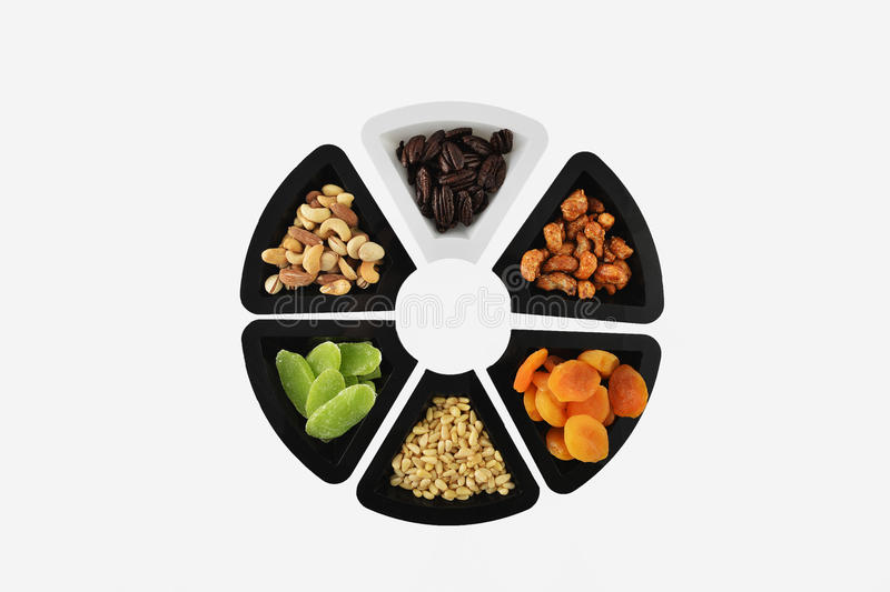 Dried fruits and almonds - symbols of Jweish holiday Tu Bishvat. Dried fruits and almonds served in plates and forming a flower shape - symbols of the Jewish stock photos