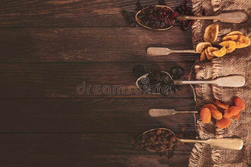 Dried fruits arranged on a spoon, fabric and an old table. Composition in the old style royalty free stock photography