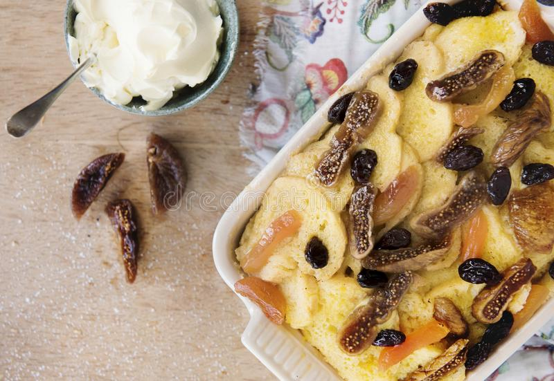 Dried fruits bread pudding with whipped cream on wooden table stock image