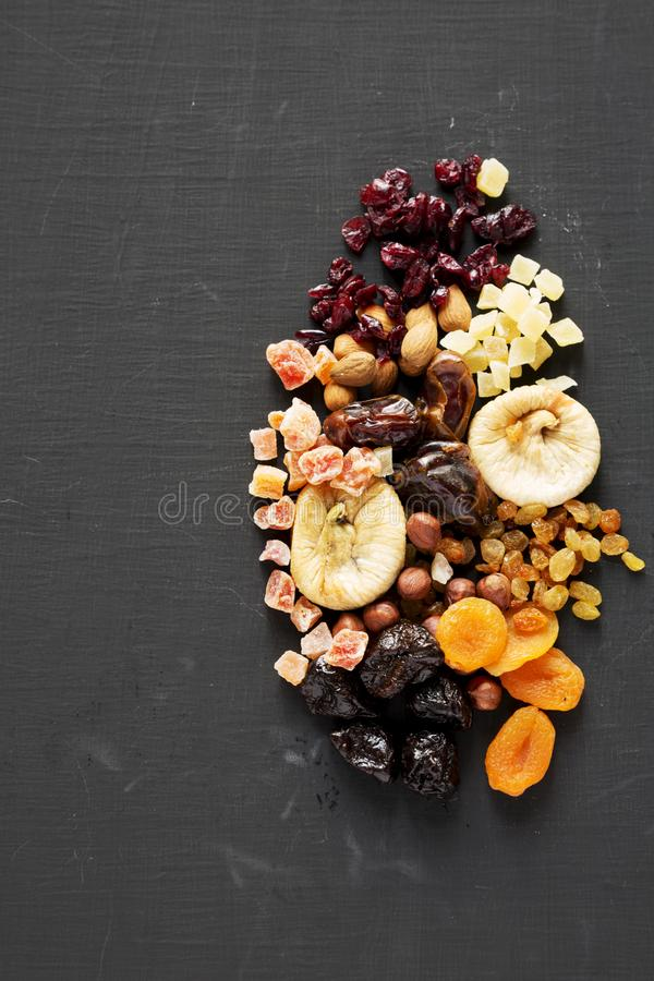 Dried fruits and nut mix on black surface, top view. Overhead. Copy space royalty free stock images