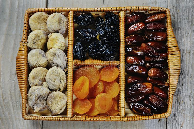 Dried fruits prunes dates apricots figs symbols of judaic holiday Tu Bishvat. In a box on a wooden background royalty free stock images