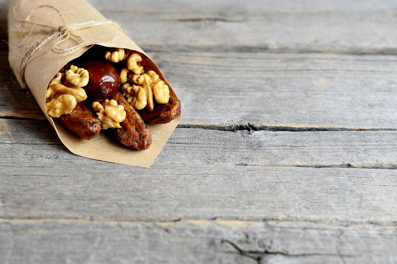 Dried fruits and raw walnuts in wrapping paper on an old wooden background with empty space for text. Dried bananas and dates royalty free stock photos