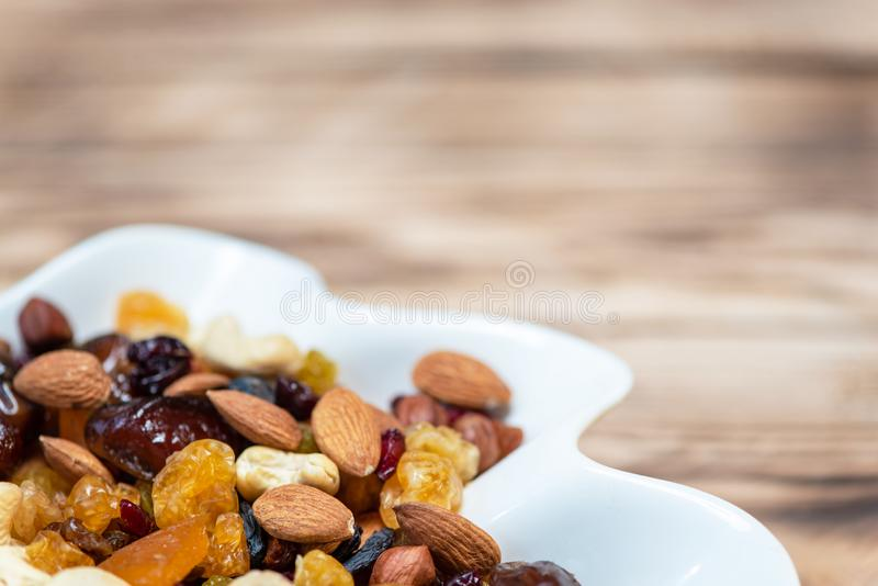 Dried fruits in white plate on wooden table, copy space for text. Mix of different varieties of nuts and berries, vitamins royalty free stock photo