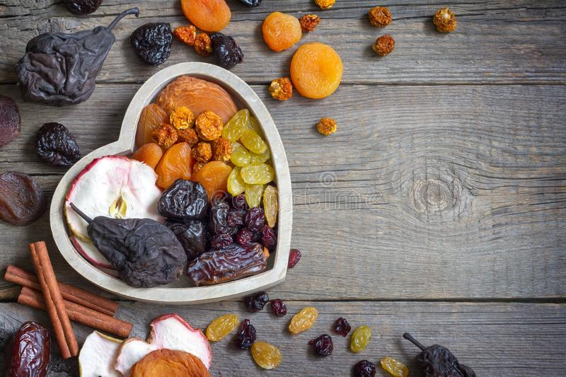 Dried fruits on wooden board in the heart food concept. Closeup stock image