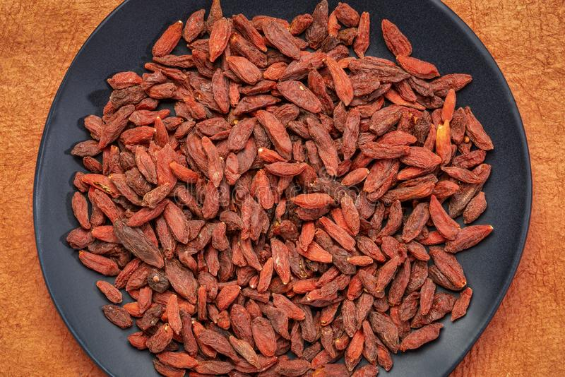 Dried goji berries on am black plate. Dried goji berries on a black ceramic plate against orange textured paper background stock image