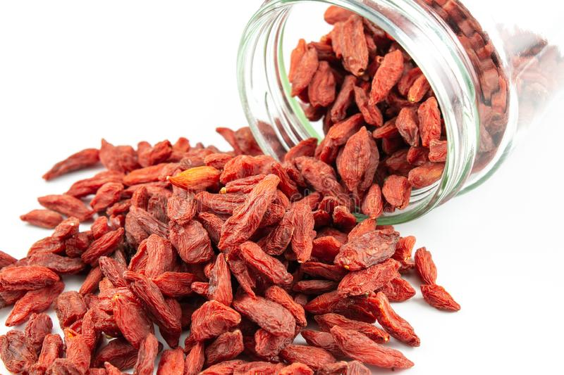Dried goji berries spilling out of glass jar stock photos