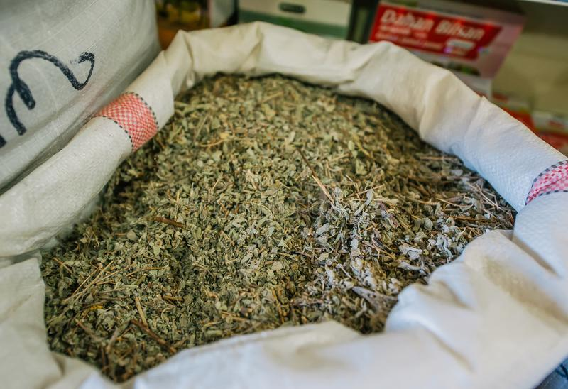 Dried green tea is in big sack in shop of spices. Closeup photo stock image