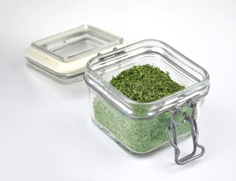 Dried herbs. In a glass storage jar royalty free stock photography