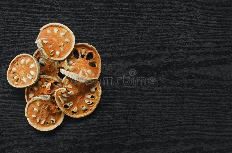 Dried herbs and dried bael fruit, Top view of bael dry on the wooden floor royalty free stock photo