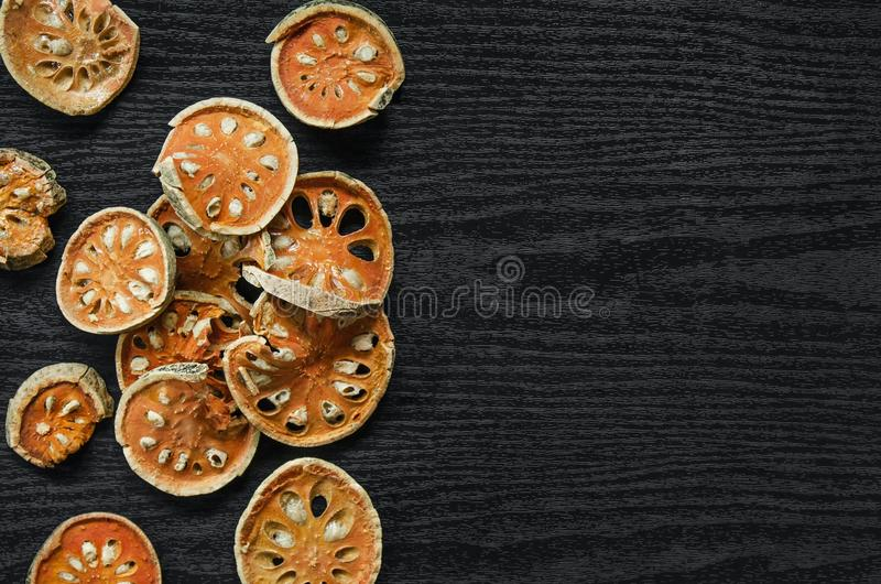 Dried herbs and dried bael fruit, Top view of bael dry on the wooden floor royalty free stock photography