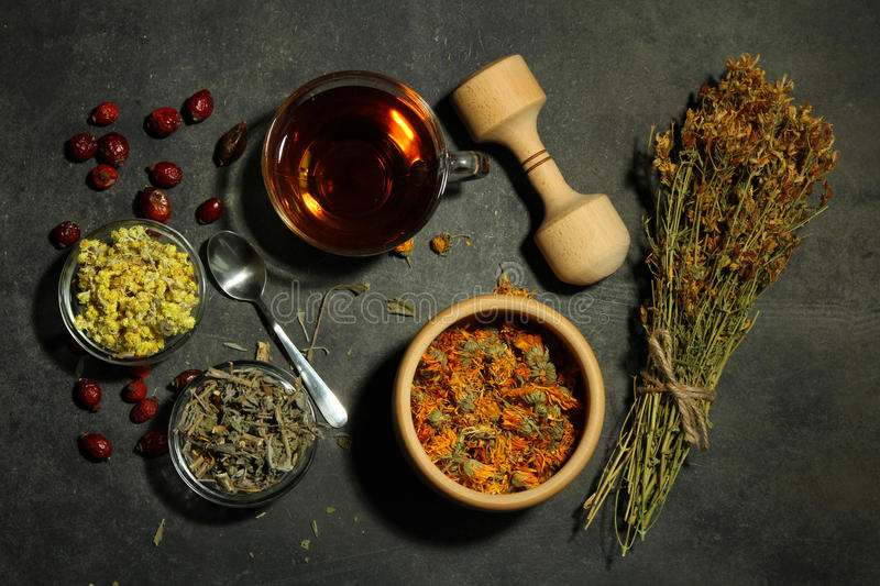 Dried herbs. Dried flowers of herbs with tea and a wooden spoon with a glass of bowl on wooden background royalty free stock photo