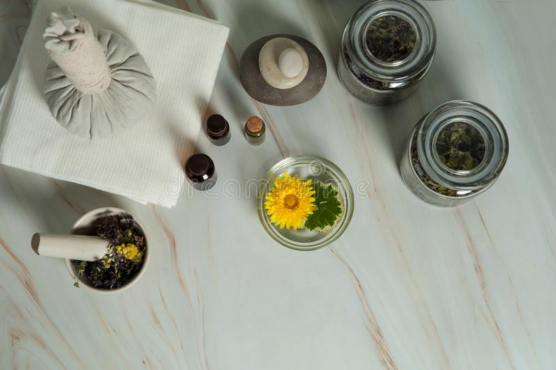 Dried herbs, small bottles of essential oils, mortar and pestle, massage herbal bag, fragrant stick on a marble background. stock image