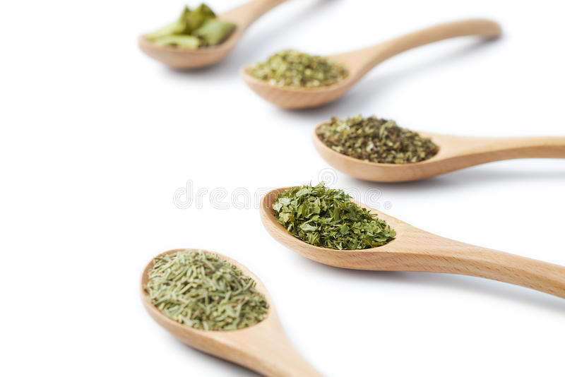 Dried Herbs on Wooden Spoons. Wooden spoon filled with dried herbs on white background stock image