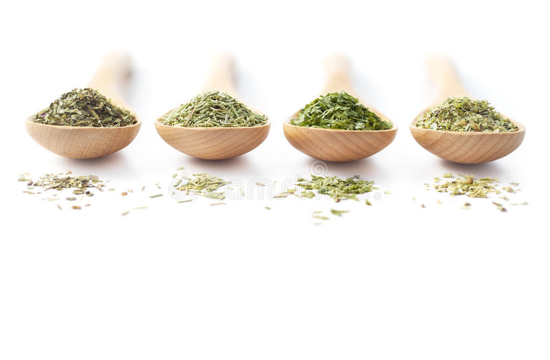 Dried Herbs on Wooden Spoons. Wooden spoon filled with dried herbs on white background stock photo