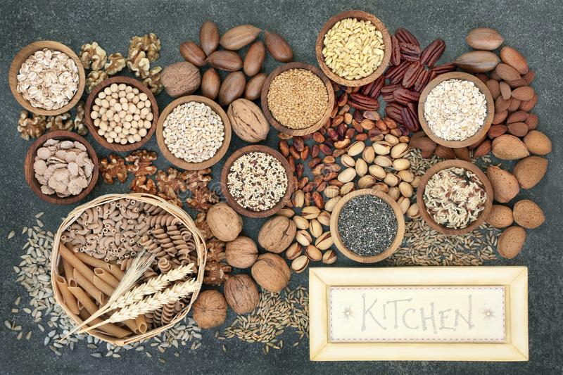 Dried High Fiber Health Food. Concept with whole wheat pasta, grains, cereals, legumes, nuts and seeds with rustic kitchen sign. Foods high in omega 3 fatty royalty free stock photo