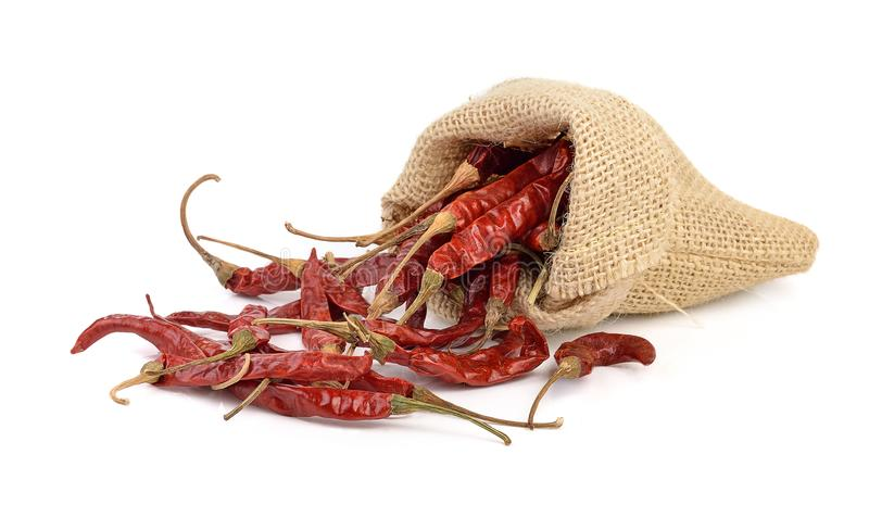 Dried hot red chillies in a sack on white bcackgroud stock photo