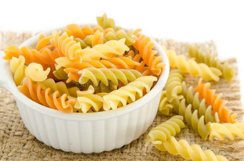 Dried italian pasta (macaroni) in white bowl. Dried italian pasta (macaroni) in white bowl on sack background stock photography