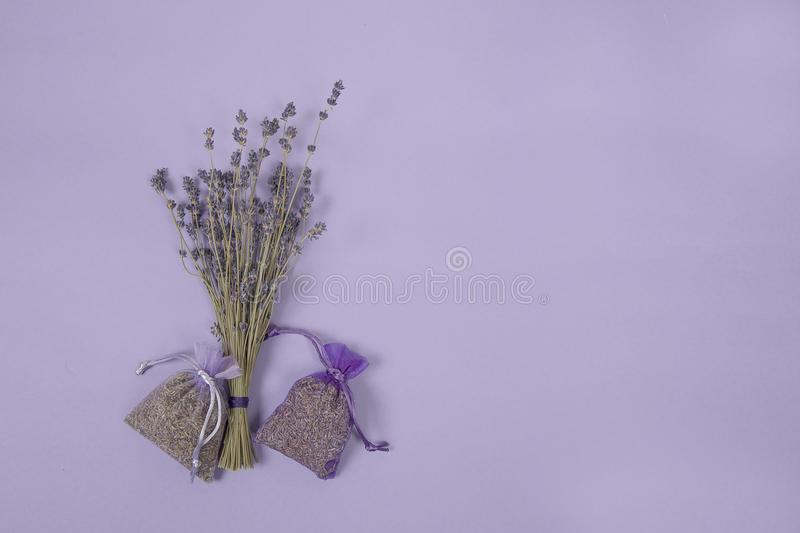 Dried lavander flowers and lavender sachets on a lavender colored background. Bunch of dried lavander flowers and lavender sachets on a lavender colored stock images