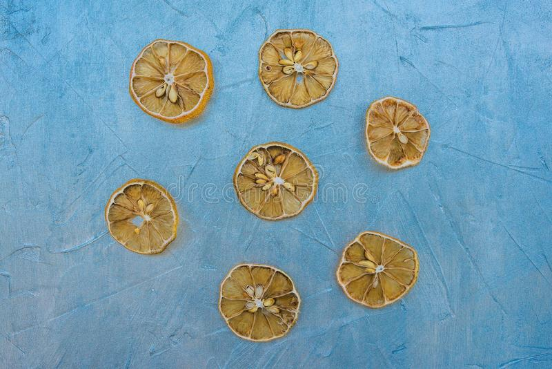 Dried lemon slices on a blue background. Sliced lemon wedges. Cooking compote or juice from dried fruit. Brewing tea with lemon. stock photos