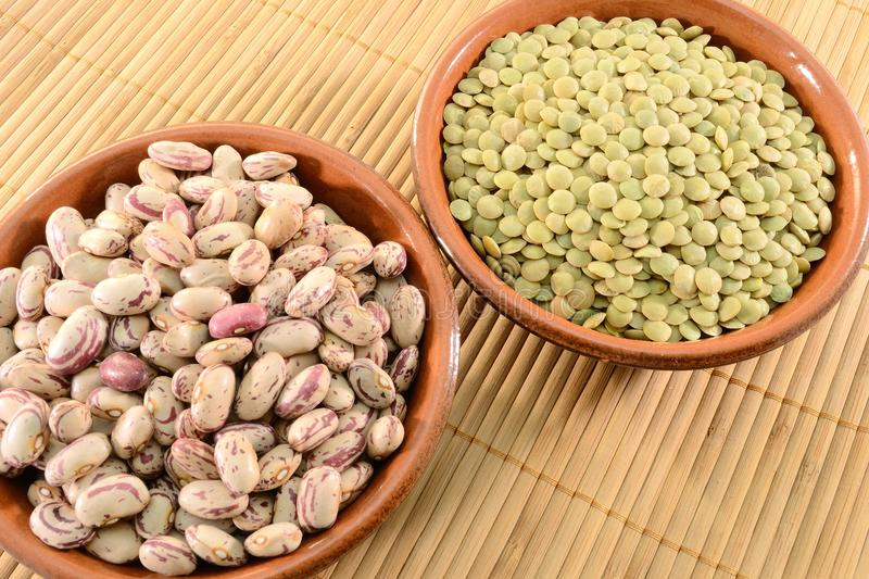 Dried lentils and beans. In a bowl on a bamboo mat royalty free stock images