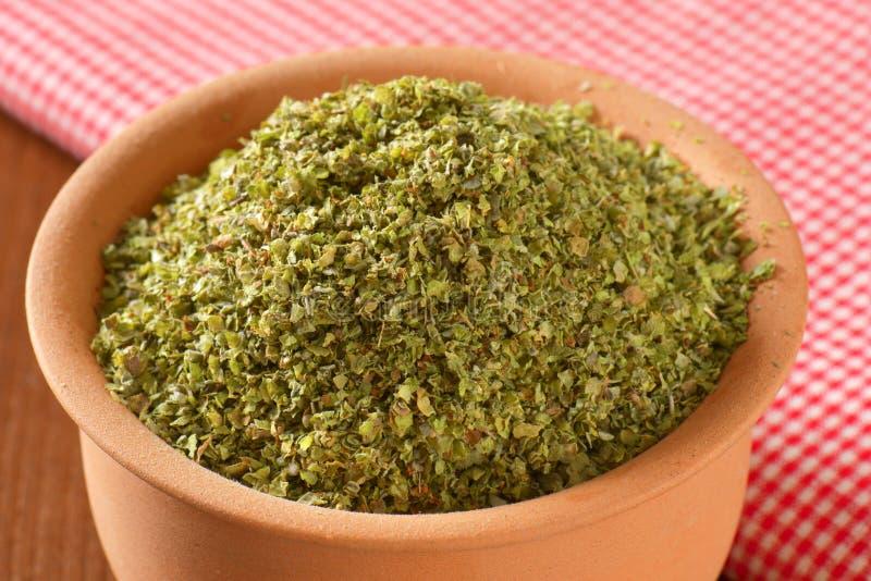 Dried Marjoram leaves. Heap of dried Marjoram leaves in terracotta bowl stock image