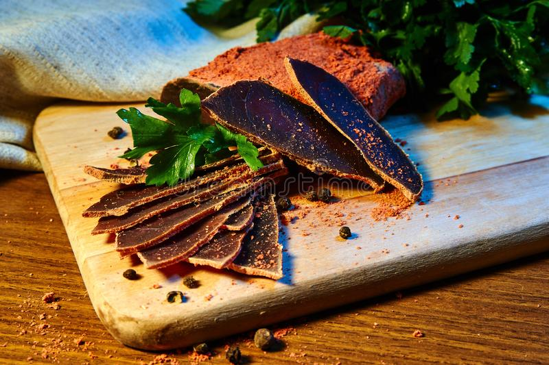 Dried meat, basturma lies on a wooden Board with capers and spices. fresh parsley royalty free stock photography