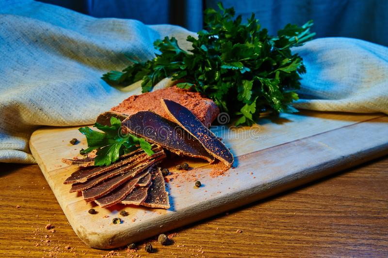 Dried meat, basturma lies on a wooden Board with capers and spices. fresh parsley royalty free stock photo