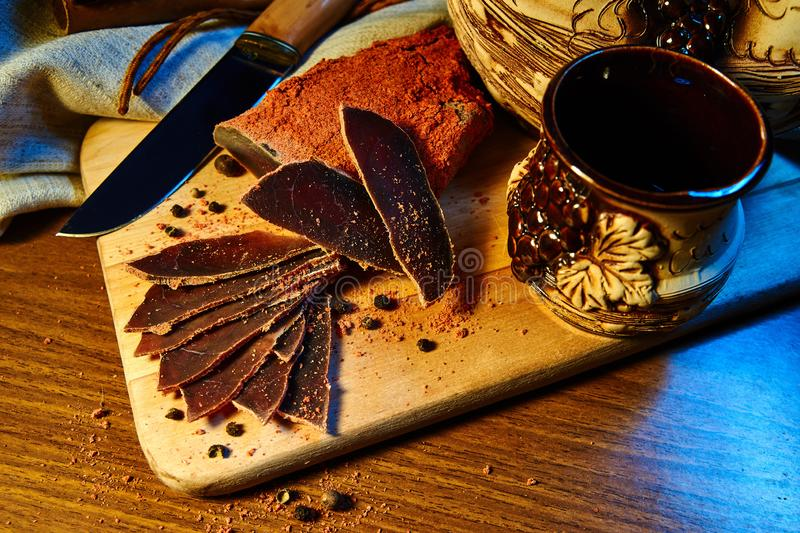 Dried meat, basturma lies on a wooden Board with capers and spices. Nearby is a clay jug and a mug stock photos