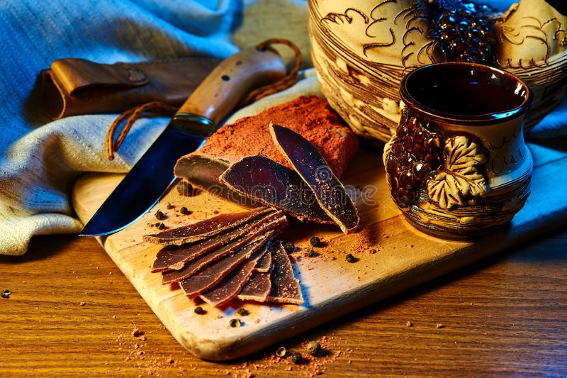 Dried meat, basturma lies on a wooden Board with capers and spices. Nearby is a clay jug and a mug stock images