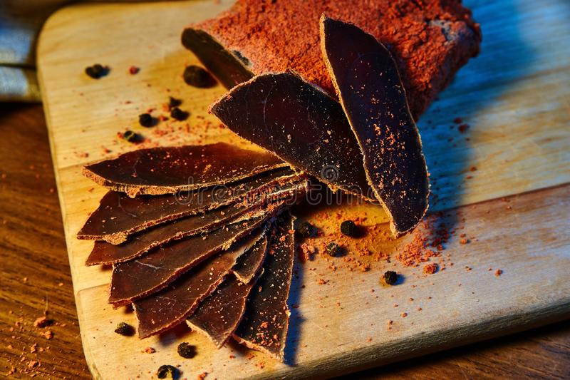 Dried meat, basturma lies on a wooden Board with capers and spices royalty free stock photos