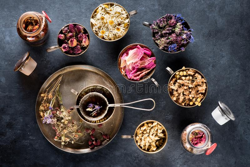 Dried medicinal herbs and flowers for herbal tea. Dried medical healing herbs and herbal tea in metal cups stock image
