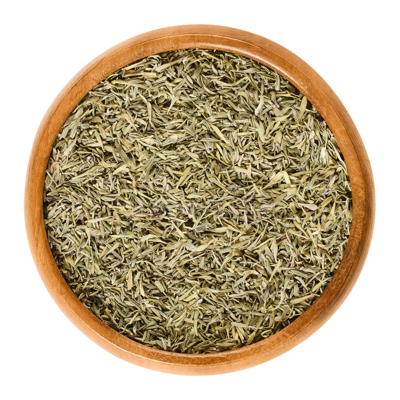 Dried minced thyme in wooden bowl over white royalty free stock images