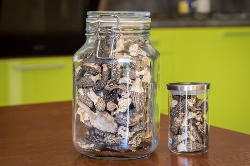 Dried morels in glasses on wooden table in kitchen stock image