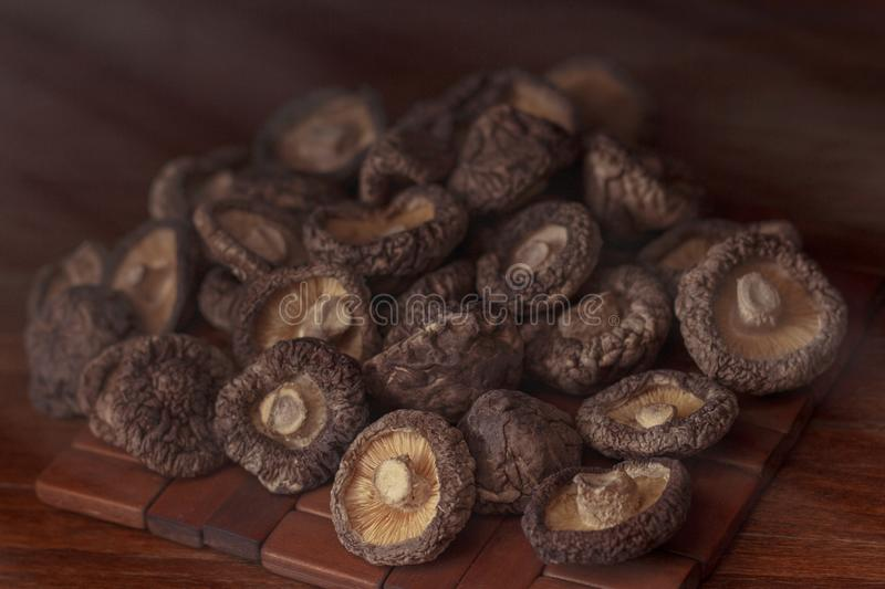 Dried mushrooms lie on a wooden dark colored surface. And blackboard royalty free stock images