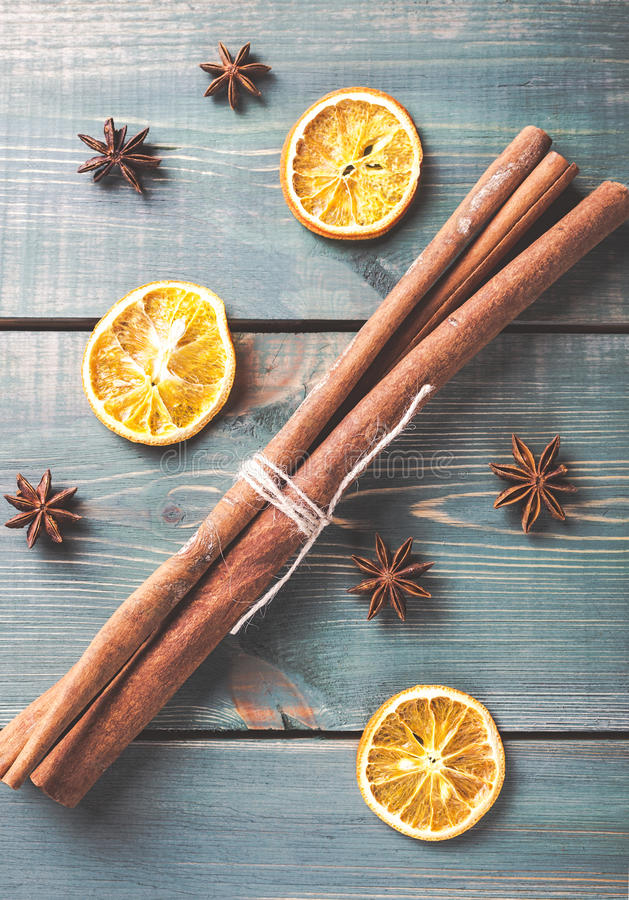 Dried orange, anise and cinnamon sticks on green wooden table. royalty free stock photography