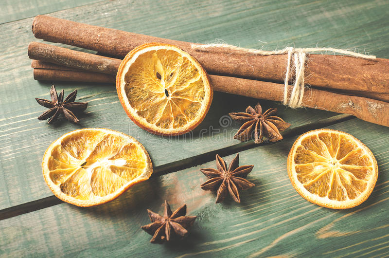 Dried orange, anise and cinnamon sticks on green wooden table. stock images