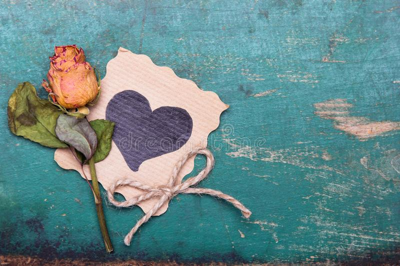Dried orange roses and heart drawing on wooden background, royalty free stock photo