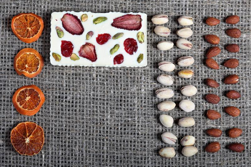 Dried orange slices, pistachios and almonds are lined up in rough linen fabric. White chocolate decorated with dried fruit.  stock photos