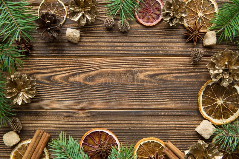 Dried oranges, golden cones and spice Christmas background. Brown sugar with anise stars and cinnamon sticks on brown wooden royalty free stock image