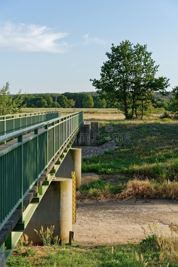 Dried-out riverbed. The river `Schwarze Elster` near Senftenberg has dried up, consequence of the hot summer 2019, view of the waterless riverbed near a bridge royalty free stock images