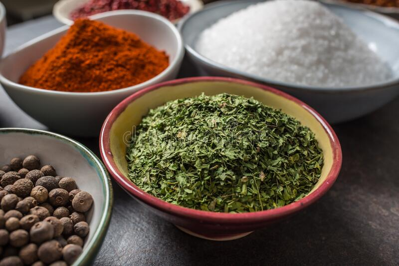 Dried parsley and variety spices and herbs in bowls royalty free stock photography
