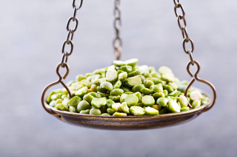 Dried peas in a balance scale royalty free stock images