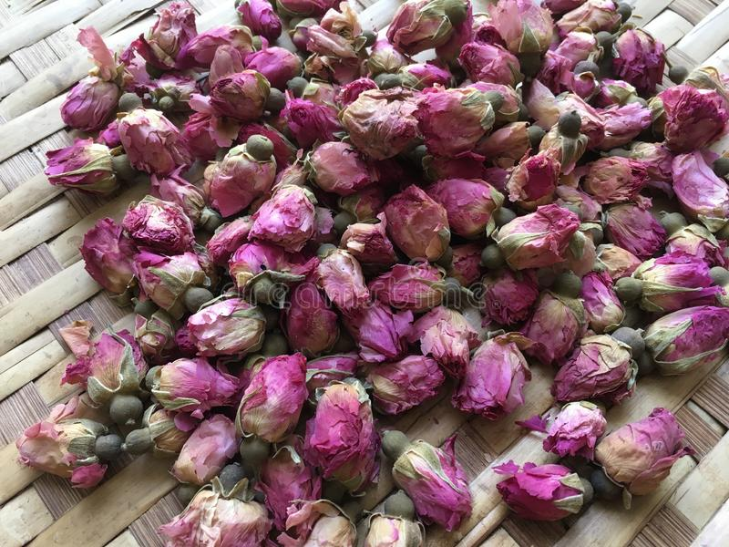Dried pink Damask rosebuds on bamboo flat basket stock images