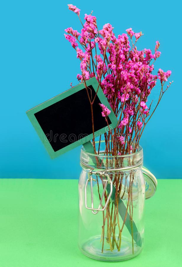 Dried pink flowers in a hermetic jar on a blue and green background. Rustic slate message board in tucked into to arrangement royalty free stock images