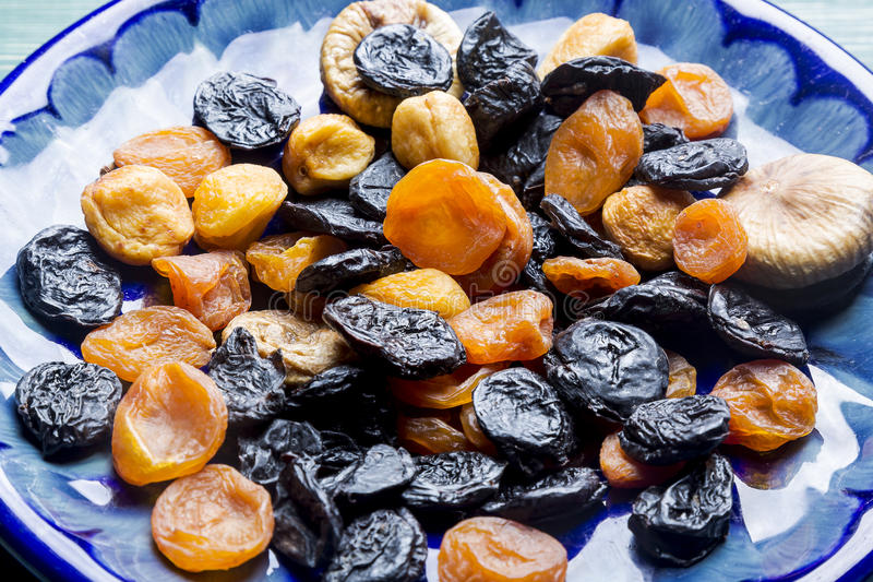 Dried plums and apricots on blue plate stock photos