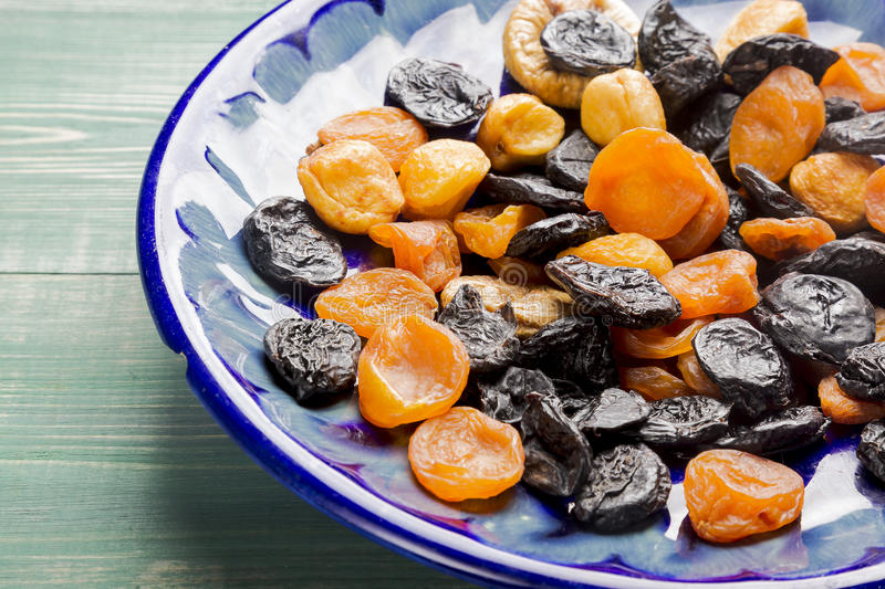 Dried plums and apricots on blue plate and green wooden table royalty free stock photography