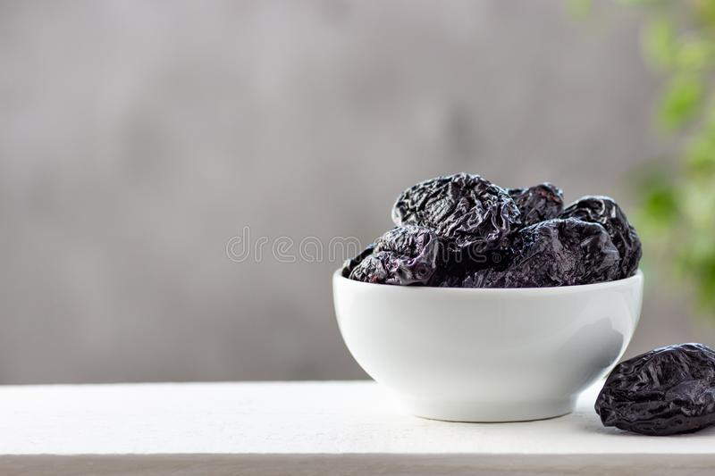 Dried prunes in a white bowl royalty free stock photography